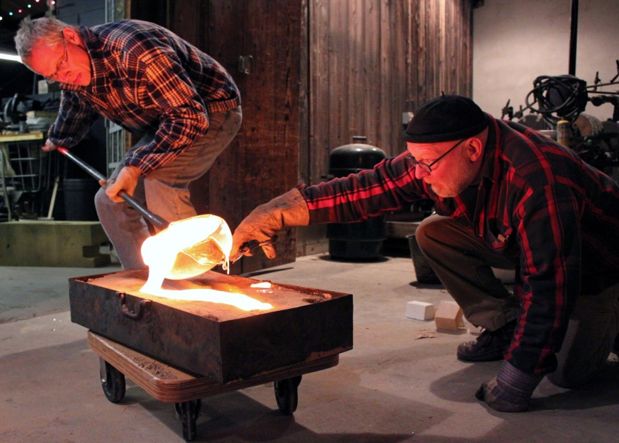 Creative Glass Center of America's Studio Creative Director Hank Adams (L) and Jack Larimore casting.
