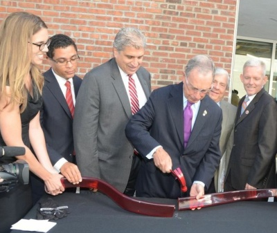 While UrbanGlass executive director Cybele Maylone and elected officials look on, New York mayor Michael Bloomberg breaks a glass ribbon to mark the reopening of UrbanGlass.